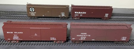 Four newly decaled box cars. A gloss coat was applied after the decals were dry. When th egloss coat was dry, a flat coat was applied as preparation for weathering.